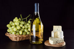 Garrafa de vinho, uvas em uma cesta de vime e queijo azul Imagens de Stock