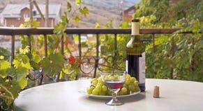 Garrafa de vinho, vidro de vinho e uvas em uma mesa redonda Balcão, envolvido com folhas da uva Imagem de Stock Royalty Free