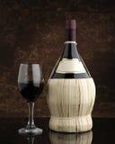 Garrafa de vino rojo con el vidrio Fotografía de archivo