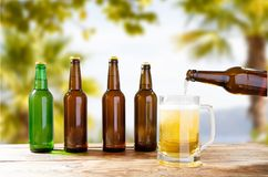 A garrafa derrama a cerveja em um vidro, garrafas na tabela de madeira no fundo tropical borrado foto de stock royalty free