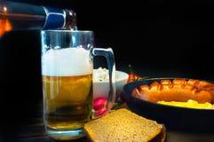 A garrafa derrama a cerveja espumoso em um vidro entre um jantar delicioso imagens de stock royalty free