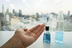 A garrafa do álcool e a mão anti-bacteriana coagulam-se na mão da mulher Imagem de Stock Royalty Free