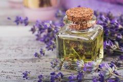A garrafa do óleo essencial e da alfazema fresca floresce Foto de Stock Royalty Free