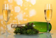 A garrafa do champanhe do ano novo encontra-se na tabela perto dos ramos do pinho com cones do pinho e dois vidros de vinho compl Imagem de Stock Royalty Free