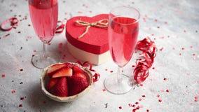 Garrafa do champanhe cor-de-rosa, dos vidros com morangos frescas e do presente dado forma coração filme