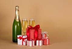 Garrafa do champanhe, dois vidros, lote de presentes do Natal em umas caixas coloridas no bege Fotos de Stock Royalty Free