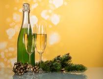 A garrafa do champanhe, dois vidros, pinho decorado ramifica no yel Fotografia de Stock Royalty Free