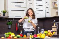 Garrafa do juise da abertura da jovem mulher na cozinha Imagem de Stock Royalty Free