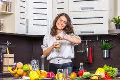 Garrafa do juise da abertura da jovem mulher na cozinha Foto de Stock Royalty Free