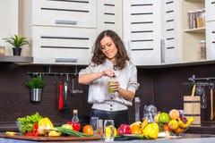 Garrafa do juise da abertura da jovem mulher na cozinha Fotografia de Stock