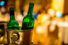 Garrafa do verde de colocação em uma cubeta de gelo Fotografia de Stock Royalty Free