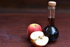Garrafa do vinagre de sidra de maçã ao lado das maçãs maduras fotografia de stock royalty free