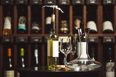 Garrafa do vinho branco na tabela ao lado do filtro e dos vidros sobre o fundo da prateleira imagem de stock royalty free
