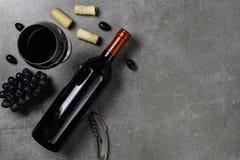 Garrafa do vinho, do cálice, das cortiça e das uvas no fundo concreto Copie o espa?o foto de stock
