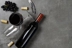 Garrafa do vinho, das bacias, das cortiça, do abridor e das uvas no fundo concreto Copie o espa?o imagem de stock royalty free