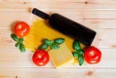 Garrafa do vinho e da massa crua dos espaguetes com tomates frescos Imagens de Stock Royalty Free