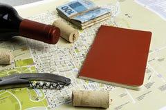 Garrafa do vinho e das corti?a no mapa para o planeamento da rota Caderno vermelho para notas foto de stock