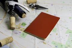 Garrafa do vinho e das corti?a no mapa para o planeamento da rota Caderno vermelho para notas imagens de stock