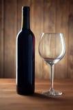 Garrafa do vinho e de um vidro na tabela de madeira velha Imagens de Stock