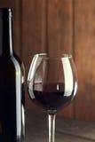 Garrafa do vinho e de um vidro na tabela de madeira velha Imagens de Stock Royalty Free
