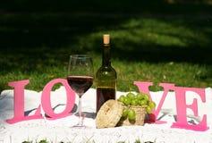 A garrafa do vinho e o vidro estão na toalha de mesa Fotos de Stock Royalty Free