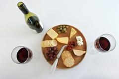 A garrafa do vinho tinto com dois copos de vinho serviu com queijo plat Fotos de Stock Royalty Free