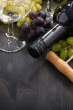 Garrafa do vinho tinto, do vidro vazio e das uvas no fundo de madeira Imagem de Stock