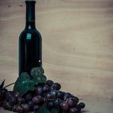 Garrafa do vinho tinto e das uvas no fundo de madeira Imagens de Stock