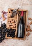 Garrafa do vinho tinto e do vidro vazio com as uvas escuras com corti?a e abridor dentro da caixa de madeira do vintage no fundo  foto de stock