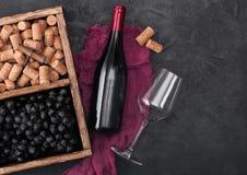 Garrafa do vinho tinto no pano vermelho com vidro vazio e as uvas escuras com corti?a e no corkscrew dentro da caixa de madeira d fotos de stock royalty free