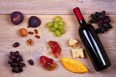 Garrafa do vinho vermelho e branco com queijo, prosciutto, figos e uva Do vinho vida ainda Alimento e conceito das bebidas Fotografia de Stock Royalty Free