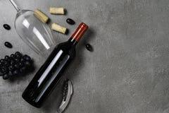 Garrafa do vinho, do vidro, do abridor, das cortiça e das uvas no fundo concreto Copie o espa?o imagens de stock royalty free
