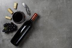 Garrafa do vinho, do vidro, das cortiça, do abridor e das uvas no fundo concreto Copie o espa?o foto de stock royalty free