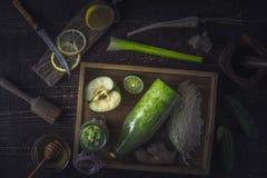 Garrafa e frasco com o batido na bandeja de madeira com os ingredientes diferentes na tabela de madeira Fotografia de Stock Royalty Free