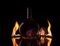 A garrafa e o vidro do vinho no fogo ardem Fotografia de Stock Royalty Free