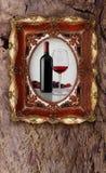 A garrafa e o vidro wine na moldura para retrato velha no fundo de madeira Foto de Stock Royalty Free
