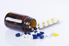Garrafa e tabuletas da medicina no fundo branco Imagem de Stock Royalty Free