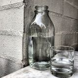 Garrafa e vidro da água imagens de stock