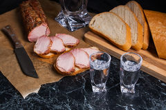 Garrafa e vidro de tiro com vodca com fatias de carne fumado em b Fotografia de Stock