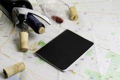 Garrafa e vidro do vinho e das cortiça no mapa para o planeamento da rota Caderno preto para notas imagem de stock royalty free