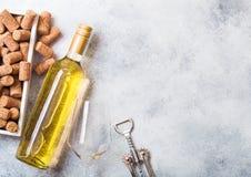 Garrafa e vidros do vinho branco com a caixa das corti?a e o abridor do crkscrew no fundo de pedra da mesa de cozinha Vista super fotografia de stock