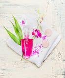 Garrafa elegante da loção, de flores cor-de-rosa da orquídea e das folhas de bambu verdes na toalha branca no fundo de madeira cl Fotos de Stock Royalty Free