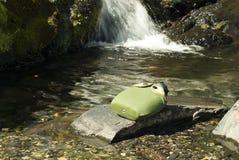 Garrafa em uma pedra na frente de um córrego da montanha fotografia de stock