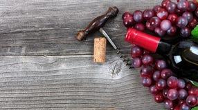 Garrafa escura do vinho tinto e das uvas em pranchas de madeira do vintage Fotos de Stock Royalty Free