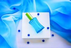 Garrafa, grânulos e matéria têxtil de vidro azuis de perfume Fotografia de Stock