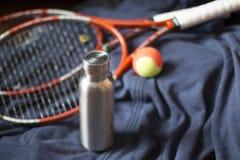 Garrafa inoxidável isolada com raquete e bola de tênis foto de stock