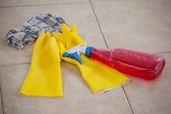 Garrafa, luva e pano detergentes do pulverizador no assoalho de telha Fotografia de Stock