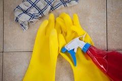 Garrafa, luva e pano detergentes do pulverizador no assoalho de telha Fotografia de Stock Royalty Free