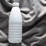 Garrafa plástica branca do iogurte em uma toalha de mesa de seda cinzenta, vista superior fotos de stock royalty free