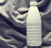 Garrafa plástica branca do iogurte em uma toalha de mesa de seda cinzenta, vista superior foto de stock royalty free